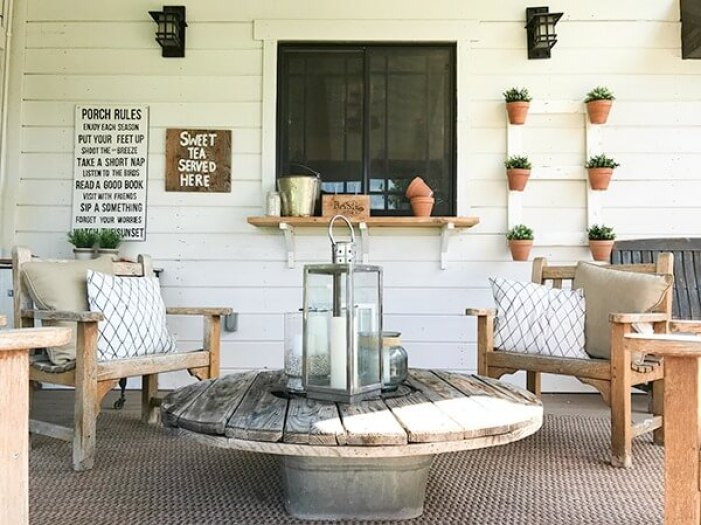 Love the teak chairs, lanterns and wire spool coffee table in this farmhouse summer porch decor!