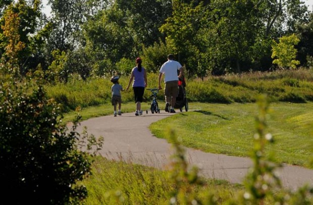 A family walks a trail in Lake Elmo Park Reserve.