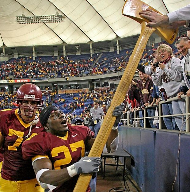 Minnesota's Eli Ward (27) hoists Paul Bunyan's Axe in celebration for the fans following the Gophers' last-second 37-34 victory over Wisconsin at the Metrodome on Saturday, Nov. 8, 2003. (Pioneer Press file photo)