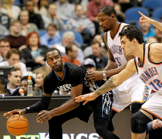 Minnesota Timberwolves forward Shabazz Muhammad, left, is pressured by Oklahoma City Thunder forward Kevin Durant, center, and Steven Adams (12) during the second quarter of an NBA basketball game in Minneapolis, Friday, Dec. 12, 2014. (AP Photo/Ann Heisenfelt)