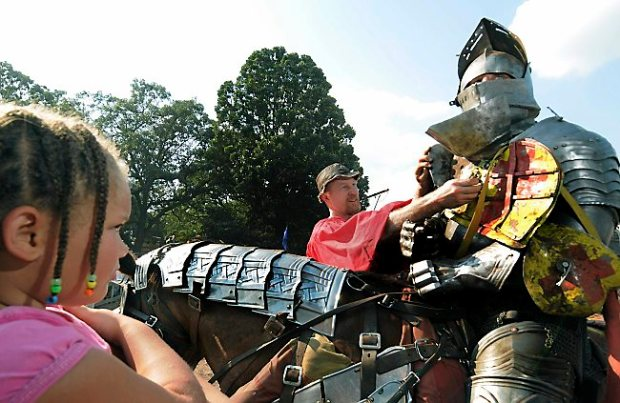 "FAMILY OUTING -- ""He's weird looking. I really don't want to talk to him,"" said nine-year-old Briyauna (cq) Willis of Milwaukee, left, who eyed Ryan Scamnon, a.k.a. Sir Orin Dayne, right, being attended by lead squire Paul Stone, center, prior to a jousting match at the Minnesota Renaissance Festival in Shakopee on Sunday September 6, 2009. (Pioneer Press: Richard Marshall)"