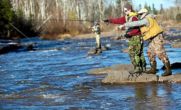 Mentor Scott Fifield of Duluth gives 15-year-old Devin Kleive a tip during the Lake Superior Steelhead Association's mentored fishing day on the Knife River near Duluth on April 18, 2015. (Clint Austin / caustin@duluthnews.com)