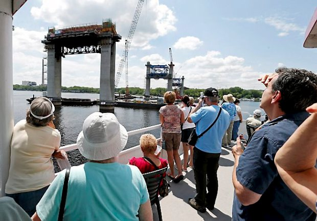 In this July 22, 2015 photo, people on the top deck of a river boat view piers toward the Minnesota side for the mile-long St. Croix Crossing bridge linking Minnesota and Wisconsin near Stillwater, Minn. Three times a month, 350 or more people head out on the 90-minute tours, with adults paying $10 apiece for the chance to view one of the biggest and most expensive bridge projects in Minnesota history. (AP Photo/Jim Mone)