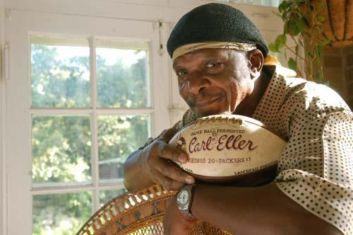 Former Minnesota Vikings defensive end Carl Eller poses in his Minneapolis home, June 24, 2004, with one of about 20 game balls he was awarded throughout his football career. Eller was a mainstay of the Vikings' dominant defensive line that helped lead the team to four Super Bowls from 1969-77, and he'll enter the Pro Football Hall of Fame on Sunday. (AP Photo/Ann Heisenfelt)