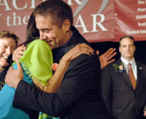 In this photo provided by Education Minnesota, Ryan Vernosh, right, is hugged by fellow finalist Regina Seabrook after being named 2010 Minnesota Teacher of the Year at a banquet in Brooklyn Park, Minn., Sunday, May 2, 2010. Vernosh is a sixth grade teacher at Maxfield Magnet School in St. Paul, Minn. Education Minnesota President Tom Dooher is at far right. (AP Photo/ Education Minnesota, Janet Hostetter)