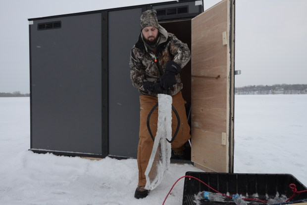 Eric Wallace of Maple Grove, Minn., removes a cunk of freshly sawed ice with an ice claw Friday , Jan. 22, 2016. (Pioneer Press: Dave Orrick)