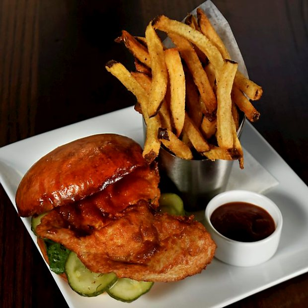 Fried chicken sandwich with cornmeal batter, spicy aioli, dill pickles, lettuce on a milk bun at the Ox Cart Ale House in St. Paul's Lowertown on Wednesday, September 30, 2015. (Pioneer Press: John Autey)