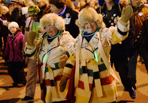 Twin sisters Joan Kelly, left, and Jane Lonergan wave to people on the sidewalks as the pair march in the Winter Carnival Moon Glow Parade in St. Paul on Thursday, Jan. 28, 2016. (Pioneer Press: John Autey)