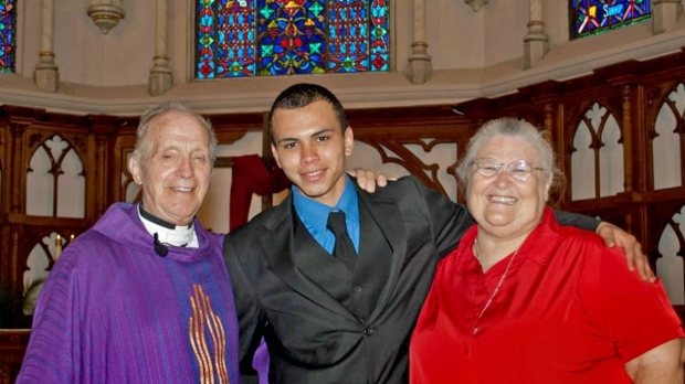 "Honduran child immigrant Yordin Alvarez, who crossed the border into the U.S. at age 12, poses with the late Rev. Robert Groschen, left, and Pat Teltschik, a former teacher at his Texas high school, after a ceremony in 2012 in which parents give their children at the school a promise ring. Groschen, who cared for Alvarez while he attended the school and bought a ring for him so he did not feel left out, died six months after the picture was taken. ""He was devastated and still wears the ring daily,"" said Groschen's niece, Karen Wilcox, who along with her husband opened their White Lake Bear home to Alvarez following the death. (Photo courtesy Karen Wilcox)"