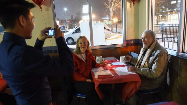 """John Lutgen, normally a kitchen worker but on this day a waiter, photographs Debrah and Tom Betz of St. Paul, celebrating Valentine's Day with a dinner at White Castle on University Avenue in St. Paul, February 14, 2016. It is the 25th year that White Castle has held the special """"Love in the Castle"""" event. (Pioneer Press: Scott Takushi)"""