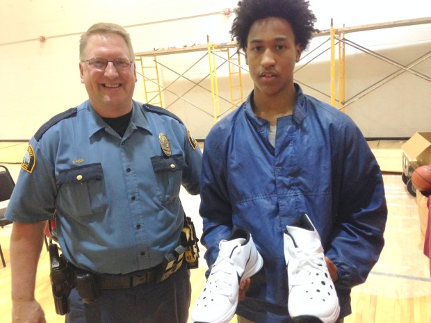 St. Paul Central High School student Dion Ford shows off the new basketball shoes he got Wednesday, April 20, 2016, through a fundraising effort organized by St. Paul Police Officer Tom Reis, left. (Pioneer Press: Jaime DeLage)
