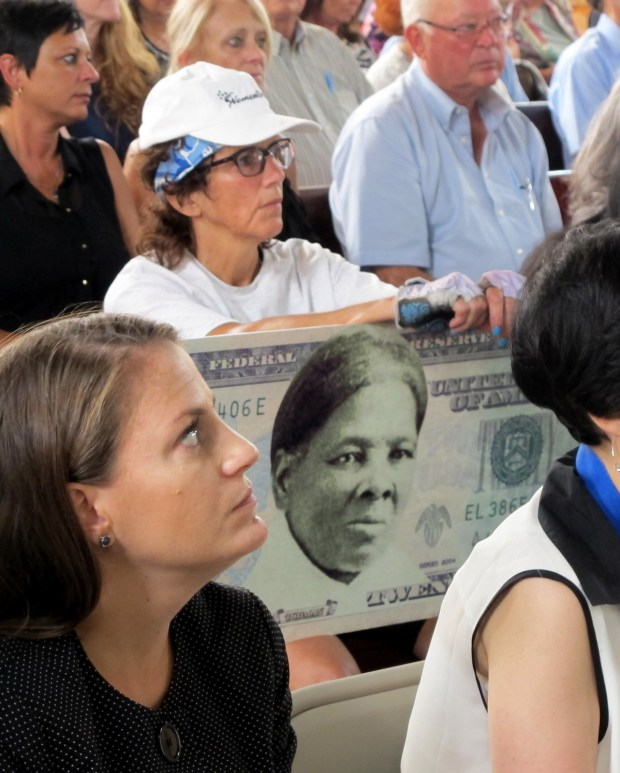 In a 2015 photo, a woman holds a sign supporting Harriet Tubman for the $20 bill during a town hall meeting at the Women's Rights National Historical Park in Seneca Falls, N.Y. A Treasury official said Wednesday, April 20, 2016, that Secretary Jacob Lew has decided to put Harriet Tubman on the $20 bill, making her the first woman on U.S. paper currency in 100 years. (AP Photo/Carolyn Thompson, File)