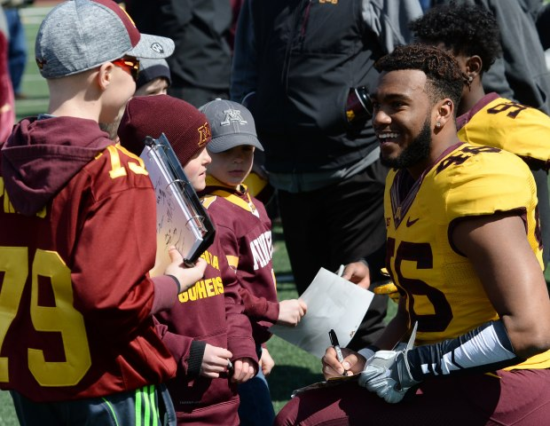 Minnesota Gophers defensive lineman Winston DeLattiboudere signs autographs for young fans after the Gophers Spring Practice game at TCF Bank Stadium on Saturday, April 9, 2016. The Gold team beat the White team, 19-7. (Pioneer Press: John Autey)