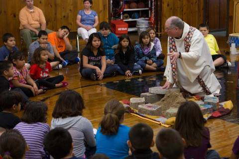 Father Jerry Rogers, center, speaks to a group of students of St. Mary's Mission and School in the Red Lake Indian reservation in a 2011 photo. Rogers has been pastor of the state's smallest and poorest Catholic parish since 2009. (Photo courtesy of St. Mary's Mission)