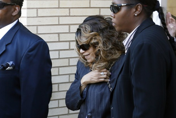Tyka Nelson, center, the sister of Prince, is escorted by unidentified people as she leaves the Carver County Courthouse Monday, May 2, 2016, in Chaska, Minn. where a judge has confirmed the appointment of a special administrator to oversee the settlement of Prince's estate. The pop rock singer died on April 21 at the age of 57. (AP Photo/Jim Mone)