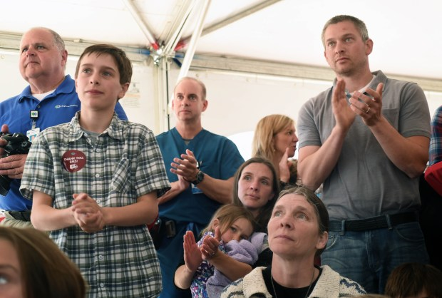 Jack Hamond, joined by his famly, from left, his mother Holly holding his sister Emma, 6, his grandmother Carol Goodwin of Monticello and his father, Steve, applaud as the Stillwater Fire Department is honored for their part in saving Jack's life. (Pioneer Press: Scott Takushi)