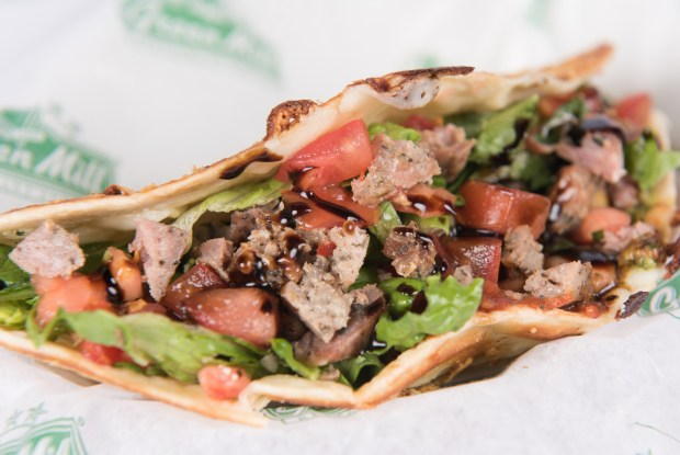 Italian taco: A flour tortilla baked with butter and shredded parmesan, filled with Italian sausage and mozzarella, topped with roasted bruschetta, romaine lettuce, Caesar dressing, pesto, pizza sauce and parmesan cheese, and then drizzled with a balsamic glaze. At Green Mill on the east side of Cooper Street, between Randall and Wright avenues, at Family Fair at Baldwin Park. (Courtesy of Minnesota State Fair)