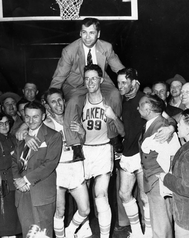 Minneapolis Lakers players, including George Mikan (99) hoist coach John Kundla and carry him to their dressing room after beating the New York Knickebockers 82-65 April 25, 1952, winning their fourth National Basketball Association title in five years. (AP Photo)
