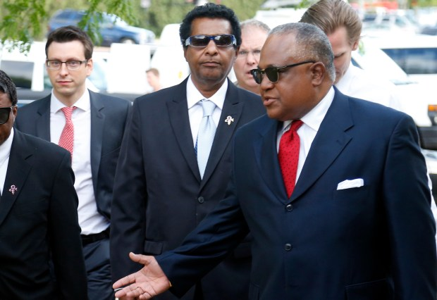 Alfred Jackson, center, the half-brother of Prince, is escorted by his attorney, Frank Wheaton, right, as he arrives Monday, June 27, 2016, at the Carver County courthouse in Chaska, Minn. for a hearing over how to verify who qualifies as Prince's heirs. (AP Photo/Jim Mone)