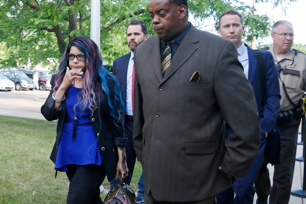 Tyka Nelson, left, the sister of the Prince, arrives at the Carver County courthouse in Chaska, Minn. Monday, June 27, 2016 with her husband, Maurice Phillips, right, and attorneys for a hearing over how to verify who qualifies as Prince's heirs. Prince died in April from an accidental painkiller overdose. (AP Photo/Jim Mone)