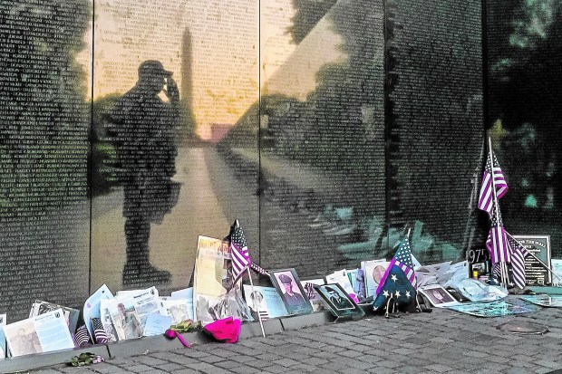 """An Army veteran stops to salute his fallen comrades during a visit to """"The Wall"""" at the Vietnam War Memorial in Washington, D.C. (Associated Press file photo)"""