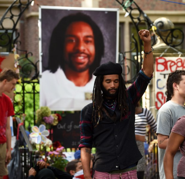 Tyler Clark Edwards of St. Paul raises his fist in the air in front of a large photo of Philando Castile, as protesters encamped in front of the Governor's Mansion on Summit Avenue in St. Paul were told by police that they must remove their stuff, stay out of the street and not block the sidewalks, Tuesday, July 26, 2016. Vehicles were allowed into the blocked off area to pick up belongings and take them away. A handful of protesters were still sitting in front of the entrance to the building at 10:00 a.m. ( Pioneer Press: Scott Takushi)