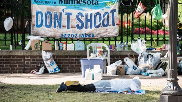 A person sleeps on the ground outside the Governor's Residence in St. Paul on Tuesday, July 12, 2016. Those protesting the fatal police shooting of Philando Castile were told Tuesday to confine their demonstration to the sidewalks outside the Summit Avenue mansion and stay off Summit Avenue. (Pioneer Press: Andy Rathbun)
