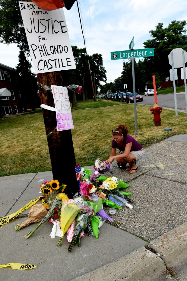 A woman places flowers across the street from where Philando Castile was killed on Larpenteur Ave. and Fry St. in Falcon Heights Thursday, July 7, 2016. Castile was killed after being shot by police during a traffic stop Wednesday night. (Pioneer Press: Jean Pieri)