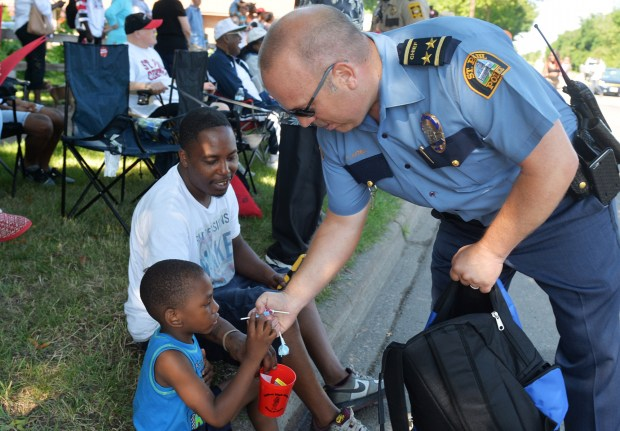 St. Paul Police Chief Todd Axtell gives Vitrella Christopher, 4-years-old, a handful of candy during the 2016 Rondo Days Parade in St. Paul on Saturday, July 16, 2016. (Pioneer Press: John Autey)