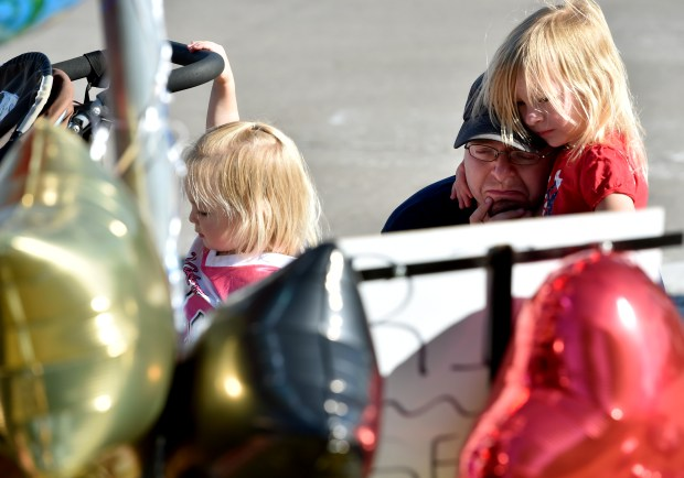 "Andrew Olson, is comforted by his daughter, Noelle, 4-years-old, left, and Sofia, 2-years-old, right the meaning of the roadside memorial for Philondo Castile at the corner of Larpenteur Avenue and Fry Street in Falcon Heights on Saturday, July 9, 2016. Olson, like many people, is still trying to understand the events of Wednesday night when Philondo Castile was shot and killed by a St. Anthony Park Police officers, two blocks from Olson's home, ""It's 2016, we shouldn't have to tell our children that people hurt other people because they are diferent."" (Pioneer Press: John Autey)"