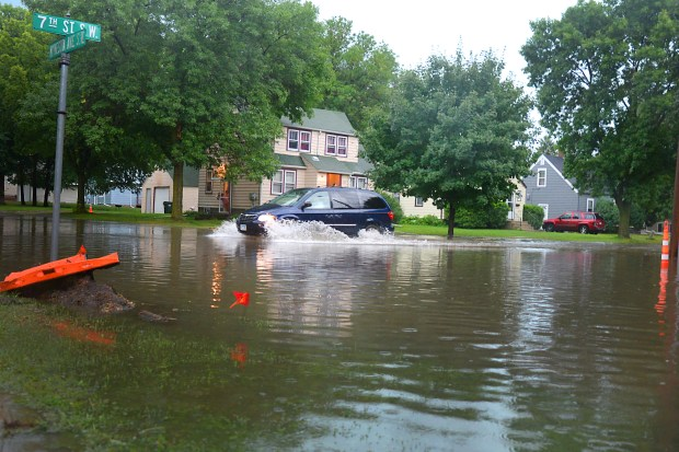 Cars push through a flooded intersection in Willmar, Minn. on Wednesday evening, Aug. 10, 2016. Willmar received 8-10 inches Wednesday evening and Thursday morning as thunderstorms moved through west-central and southern Minnesota. (Forum News Service: Briana Sanchez)