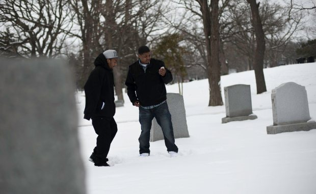 James Fields, left, and Lawrence Lyons use a photograph on Field's cell phone to try and locate the grave of Jaques Dortch in Oakland Cemetery in St. Paul, Saturday February 9, 2013. Dortch was shot and killed in 2008 while seated next to Fields in a parked car in St. Paul's Dayton's Bluff neighborhood. Fields was also shot and wounded. No one has been arrested in the case. Fields and Lyons, along with three others are the founders of the East Side Boys. (Pioneer Press: Chris Polydoroff)