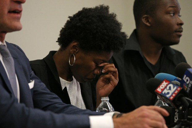 Shooting victim Paul O'Neal's sister Briana Adams, 22, briefs the media at Michael Oppenheimer's, left, law office on Aug. 5, 2016 in Chicago. The family viewed the Chicago police videos from the shooting death of Paul O'Neal early in the day at the IPRA offices with activist Ja'Mal Green, right. (Anthony Souffle/Chicago Tribune/TNS)