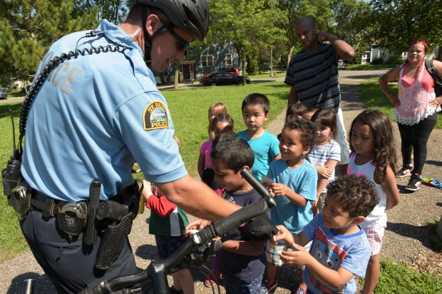 Bicycle patrol officer David Ratley hands out stickers to the kids from the Hamline Childcare Development Program as he and Officer Jason Bain ride through the Midway neighborhood near Snelling and University Avenues, in St. Paul, August 17, 2016. (Pioneer Press: Scott Takushi)
