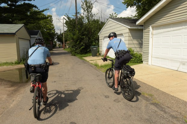 Bicycle patrol officers Jason Bain, right, and David Ratley ride through an alley in the Midway neighborhood near Snelling and University Avenues, in St. Paul, August 17, 2016. (Pioneer Press: Scott Takushi)