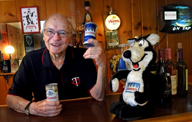 In his basement bar area, Pat Bowlin, shows the original Hamm's can with the trees before the emblem was changed to a lion. The stuffed Hamm's bear from the 1950s has a transistor radio in the back of it. He is a longtime Hamm's employee who began working in the brewery during its heyday in the 1950s, has been collecting Hamm's memorabilia since his retirement, in St. Paul on Wednesday, August 17, 2016. (Pioneer Press: Jean Pieri)