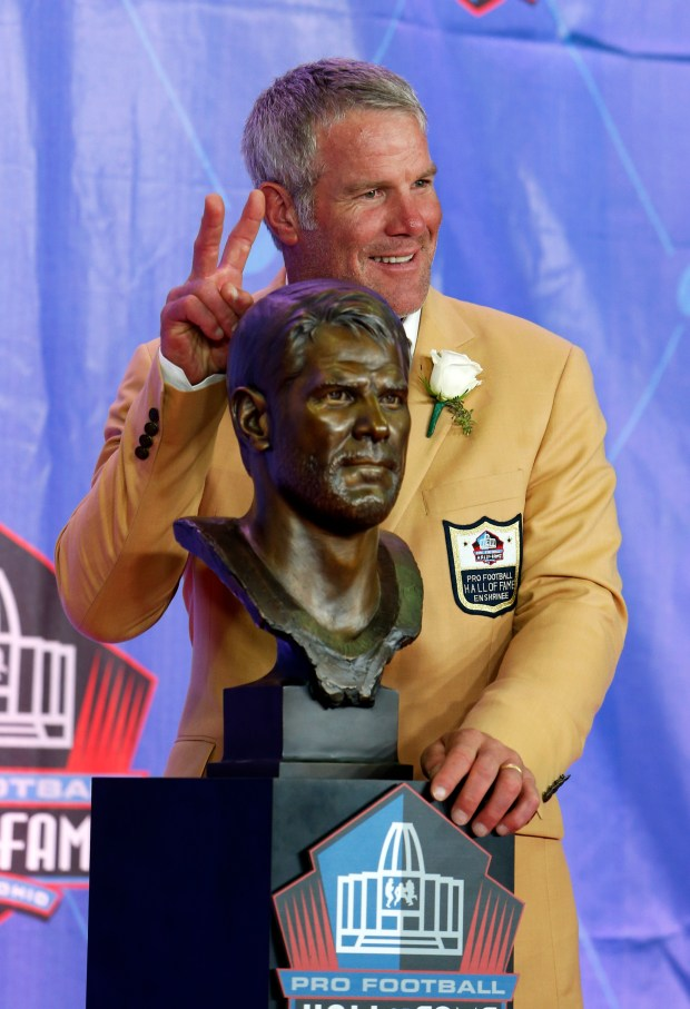 Former NFL quarterback Brett Favre poses with a bust of himself during an induction ceremony at the Pro Football Hall of Fame on Saturday, Aug. 6, 2016, in Canton, Ohio. (AP Photo/Ron Schwane)