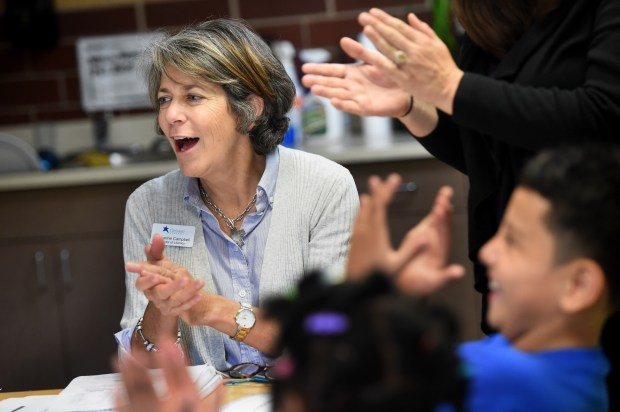 Katharine Campbell, literacy trainer from Groves Academy, claps with children after completing a reading lesson at the Al Lenzmeier West Side Boys & Girls Club in St. Paul on Thursday, Sept. 22, 2016. Boys & Girls Clubs of the Twin Cities is rolling out a pilot program to improve reading among children in first-through-third grade. (Pioneer Press: Jean Pieri)