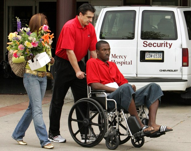 ** FILE ** Duquesne University men's basketball coach Ron Everhart, center, helps Stuard Baldonado, right, with his wheelchair after he was released from Mercy Hospital in Pittsburgh in this Sept. 22, 2006 file photo. (AP Photo/Gene J. Puskar)