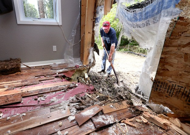 Steve Halverson, seen through the master bedroom wall, helps clean up Wednesday, Sept. 7, 2016, at the house of Tom and Tina Bjerke near Brownville, Minn., after boulders from an adjacent hillside rolled into the home shortly before 7 a.m. (Peter Thomson/La Crosse Tribune via AP)