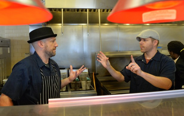 Chef Kendall Kail, left, and fellow chef and good friend Brian Titus use sign language to plan out the nights meals in the kitchen at Ward 6 on Payne Avenue in St. Paul, Tuesday, Sept. 13, 2016. Titus learned sign language after he and Kail became good friends. (Pioneer Press: John Autey)