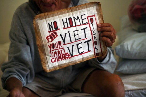 David Evansen, 68, is homeless, temporarily housed in Catholic Charities' emergency living program in Mary Hall, St. Paul, Wednesday, August 24, 2016. He shows the Pioneer Press reporter the sign he uses for panhandling. (Pioneer Press: Scott Takushi)