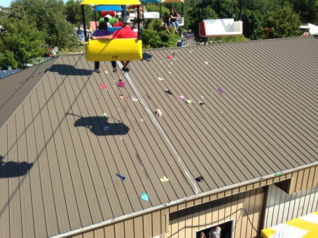 SkyGlider riders cruise above an assortment of undergarments and other items on the roof of the Little Farm Hands builidng at the Minnesota State Fair. (Richard Chin)