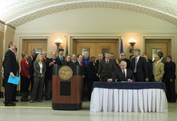 Gov. Mark Dayton signing health exchange law, in March 2013 (Archive courtesy photo)