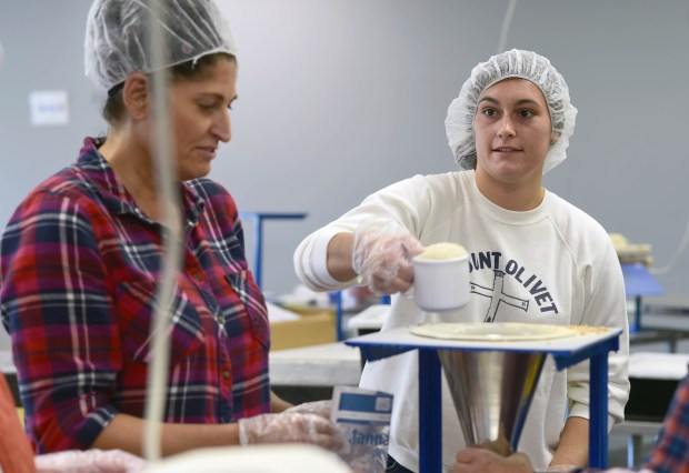 Volunteers Alison Heruth of Woodbury, left, and Megan Jelinski of Apple Valley pack bags of rice, soy, dehydrated vegetables and vitamins at Feed My Starving Children in Eagan, Minn. Monday, Oct. 17, 2016. (Pioneer Press: Scott Takushi)