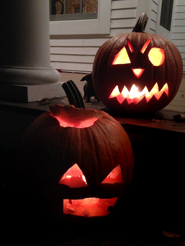 A pair of Halloween pumpkins glow from a Minneapolis porch on Oct. 31, 2014. (Pioneer Press: Neal Lambert)