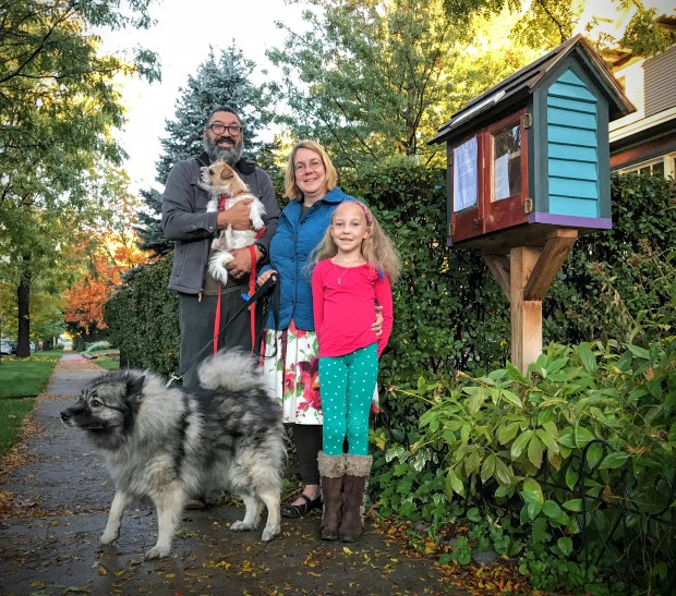 Patrick Rhone and Bethany Gladhill are shown with their daughter Beatrix and their two dogs alongside their Little Book Library. Thieves have cleaned out that book cubbie more than a dozen times in recent weeks. (Pioneer Press: Julio Ojeda-Zapata)