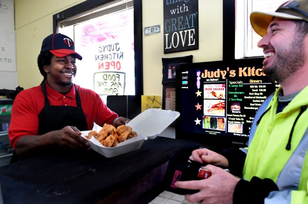 At lunchtime, Charles Dexter, left, gets ready to bag up chicken wings for Lee Salminen, a St. Paul Park and Recreation employee at Judy's Kitchen on Payne Avenue in St. Paul on Wednesday, Oct. 19, 2016. Salimen said a co-worker recommended Judy's Kitchen and that it was his first visit. Dexter named Judy's after his mother, who died of cancer last year. (Pioneer Press: Jean Pieri)