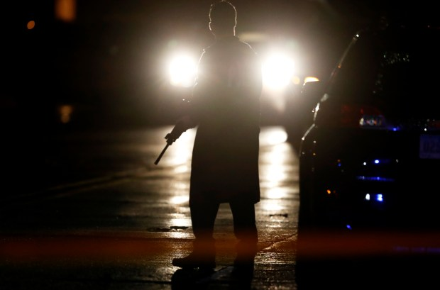 A police officer stands guard in the street at the scene of a shooting, Wednesday, Nov. 2, 2016, in Urbandale, Iowa. Two Des Moines area police officers were shot to death early Wednesday in ambush-style attacks while they were sitting in their patrol cars, and police are searching for suspects, authorities said. (AP Photo/Charlie Neibergall)