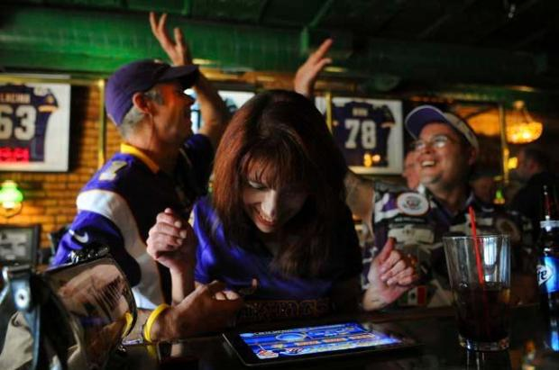 Lynn Spooner smiles as she wins at the Electonic Pull tabs while Larry Spooner, left, and Diggz Garza, both vocal Viking stadium supporter high--five in celebration at an organized media event at O'Gara's Bar and Grill in St. Paul, Minnesota, Tuesday, September 18, 2012. (Pioneer Press: John Autey)